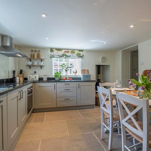 This is an example of a medium sized country kitchen/diner in Other with a submerged sink, shaker cabinets, grey cabinets, granite worktops, blue splashback, glass sheet splashback, stainless steel appliances and grey floors.
