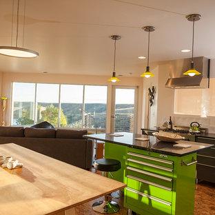 Foto på ett litet funkis linjärt kök och matrum, med en undermonterad diskho, släta luckor, grå skåp, bänkskiva i täljsten, vitt stänkskydd, stänkskydd i keramik, rostfria vitvaror, plywoodgolv och en köksö