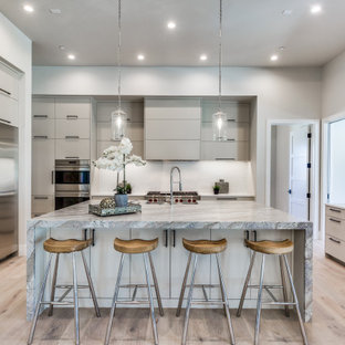 Large mediterranean kitchen designs - Inspiration for a large mediterranean l-shaped light wood floor kitchen remodel in Dallas with a drop-in sink, flat-panel cabinets, white cabinets, marble countertops, white backsplash, stainless steel appliances, an island and multicolored countertops