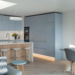 Mid-sized scandinavian l-shaped eat-in kitchen in Other with louvered cabinets, blue cabinets, quartzite benchtops, white splashback, stainless steel appliances, light hardwood floors, with island and white benchtop.
