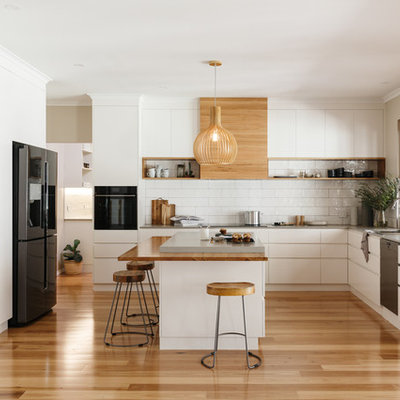 Example of a trendy l-shaped medium tone wood floor and beige floor open concept kitchen design in Adelaide with an undermount sink, flat-panel cabinets, white cabinets, white backsplash, white appliances and an island