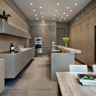 Inspiration for a contemporary u-shaped eat-in kitchen in Cheshire with an integrated sink, flat-panel cabinets, grey cabinets, stainless steel benchtops, stainless steel appliances and with island.