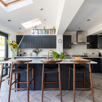 Kitchen - mid-sized contemporary l-shaped gray floor kitchen idea in London with recessed-panel cabinets, blue cabinets, marble countertops, white backsplash, subway tile backsplash, stainless steel appliances and a peninsula