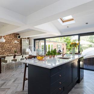 Inspiration för mellanstora moderna kök och matrum, med luckor med infälld panel, blå skåp, marmorbänkskiva, en halv köksö och grått golv