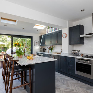 Design ideas for a contemporary kitchen/diner in London with shaker cabinets, blue cabinets, white splashback, metro tiled splashback, stainless steel appliances, light hardwood flooring, an island, grey floors and grey worktops.