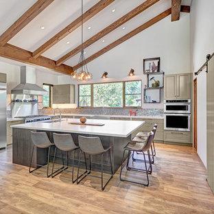 Idéer för ett stort lantligt vit kök, med en rustik diskho, luckor med infälld panel, gröna skåp, bänkskiva i kvarts, stänkskydd med metallisk yta, stänkskydd i mosaik, rostfria vitvaror, vinylgolv, en köksö och brunt golv