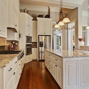 Offene, Mittelgroße Klassische Küche in L-Form mit profilierten Schrankfronten, weißen Schränken, Granit-Arbeitsplatte, Küchenrückwand in Beige, Rückwand aus Steinfliesen, Küchengeräten aus Edelstahl, braunem Holzboden und Kücheninsel in New Orleans