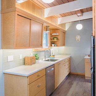 グランドラピッズの小さいミッドセンチュリースタイルのおしゃれなキッチン (フラットパネル扉のキャビネット、淡色木目調キャビネット、ラミネートカウンター、グレーのキッチンパネル、ガラスタイルのキッチンパネル、シルバーの調理設備の、無垢フローリング、アイランドなし、シングルシンク、白いキッチンカウンター) の写真