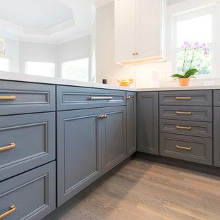 サンフランシスコの大きいエクレクティックスタイルのおしゃれなキッチン (エプロンフロントシンク、落し込みパネル扉のキャビネット、グレーのキャビネット、クオーツストーンカウンター、白いキッチンパネル、セラミックタイルのキッチンパネル、黒い調理設備、無垢フローリング、グレーの床、白いキッチンカウンター) の写真