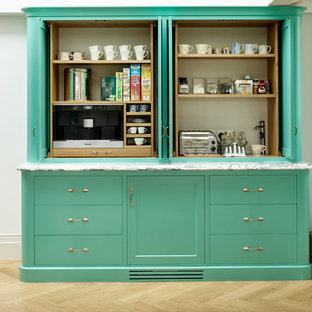 Photo of a farmhouse kitchen pantry in Kent with flat-panel cabinets, green cabinets and light hardwood flooring.