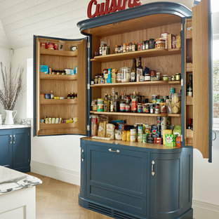 Farmhouse kitchen pantry in Kent with recessed-panel cabinets, blue cabinets and light hardwood flooring.