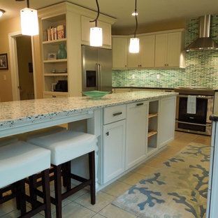 This is an example of a mid-sized beach style u-shaped open plan kitchen in Charleston with an undermount sink, recessed-panel cabinets, white cabinets, recycled glass benchtops, green splashback, glass tile splashback, stainless steel appliances, ceramic floors and with island.