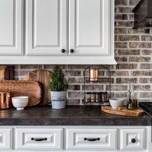 ヒューストンの広いトランジショナルスタイルのおしゃれなキッチン (エプロンフロントシンク、レイズドパネル扉のキャビネット、白いキャビネット、コンクリートカウンター、マルチカラーのキッチンパネル、レンガのキッチンパネル、シルバーの調理設備、トラバーチンの床、マルチカラーの床) の写真