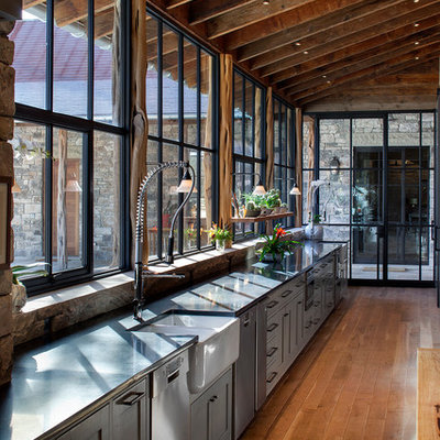Example of a mountain style single-wall medium tone wood floor kitchen design in Austin with a farmhouse sink, gray cabinets, shaker cabinets and stainless steel appliances