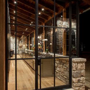 Diseño de cocina de galera, rural, con fregadero sobremueble, puertas de armario grises, electrodomésticos de acero inoxidable, suelo de madera en tonos medios y una isla