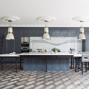 Traditional galley kitchen in London with beaded cabinets, blue cabinets, white splashback, stainless steel appliances, an island and marble splashback.