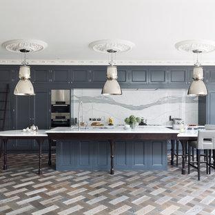 Zweizeilige Klassische Küche mit Kassettenfronten, blauen Schränken, Küchenrückwand in Weiß, Küchengeräten aus Edelstahl, Kücheninsel und Rückwand aus Marmor in London