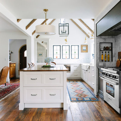 Inspiration for a mid-sized country l-shaped dark wood floor open concept kitchen remodel in Grand Rapids with a farmhouse sink, recessed-panel cabinets, white backsplash, subway tile backsplash, an island, white cabinets, stainless steel appliances and wood countertops
