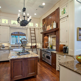Large elegant u-shaped medium tone wood floor and brown floor enclosed kitchen photo in Houston with recessed-panel cabinets, white cabinets, stainless steel appliances, a farmhouse sink, granite countertops, subway tile backsplash, an island and white backsplash
