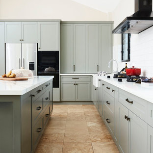 Inspiration for a large traditional l-shaped kitchen/diner in Sydney with a belfast sink, shaker cabinets, green cabinets, engineered stone countertops, white splashback, ceramic splashback, black appliances, travertine flooring, an island, yellow floors and white worktops.