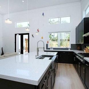 Modelo de cocina minimalista con una isla, puertas de armario negras, suelo de madera clara, fregadero sobremueble, encimera de cuarzo compacto, salpicadero negro, salpicadero de piedra caliza y electrodomésticos de acero inoxidable