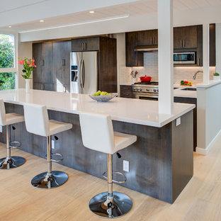 Foto di una cucina moderna di medie dimensioni con lavello sottopiano, ante lisce, top in quarzo composito, elettrodomestici in acciaio inossidabile, isola, top bianco, ante in legno bruno, paraspruzzi bianco, parquet chiaro e pavimento beige