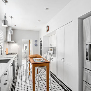 Design ideas for a mid-sized traditional galley separate kitchen in Sydney with an undermount sink, recessed-panel cabinets, white cabinets, solid surface benchtops, marble splashback, stainless steel appliances, ceramic floors, white benchtop, with island, white splashback and white floor.