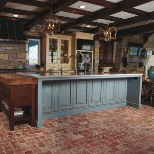 シカゴの大きいおしゃれなキッチン (ベージュのキャビネット、ベージュキッチンパネル、レンガのキッチンパネル、レンガの床、赤い床、グレーのキッチンカウンター) の写真