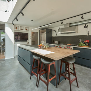 Medium sized industrial l-shaped kitchen in London with flat-panel cabinets, grey cabinets, concrete worktops, black splashback, stainless steel appliances, concrete flooring, an island, grey floors and grey worktops.