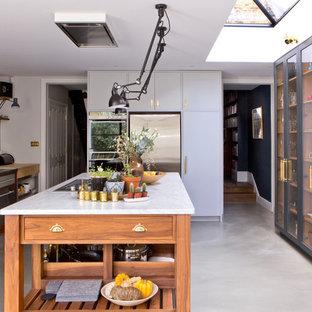 На фото: параллельная кухня-гостиная в современном стиле с монолитной раковиной, стеклянными фасадами, черными фасадами, мраморной столешницей, белым фартуком, фартуком из плитки кабанчик, техникой из нержавеющей стали, бетонным полом, островом и серым полом с
