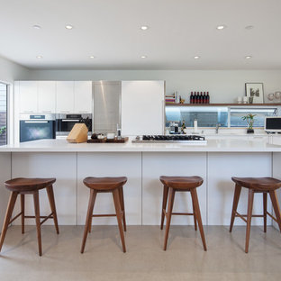 Mid-sized modern kitchen designs - Kitchen - mid-sized modern l-shaped beige floor kitchen idea in Los Angeles with flat-panel cabinets, white cabinets, paneled appliances and an island