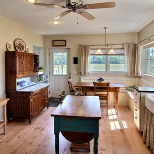 Eat-in kitchen - mid-sized country l-shaped light wood floor eat-in kitchen idea in Grand Rapids with a farmhouse sink, soapstone countertops, white cabinets, stainless steel appliances, shaker cabinets and an island