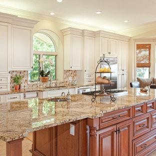 マイアミの大きいトラディショナルスタイルのおしゃれなキッチン (アンダーカウンターシンク、レイズドパネル扉のキャビネット、御影石カウンター、シルバーの調理設備の、中間色木目調キャビネット、ベージュキッチンパネル、セラミックタイルのキッチンパネル、セラミックタイルの床、ベージュの床、茶色いキッチンカウンター) の写真