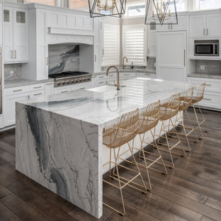 Transitional kitchen pictures - Example of a transitional l-shaped dark wood floor and brown floor kitchen design in Salt Lake City with a farmhouse sink, shaker cabinets, white cabinets, gray backsplash, paneled appliances, an island and gray countertops