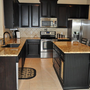 Example of a mid-sized arts and crafts l-shaped ceramic floor and beige floor eat-in kitchen design in Dallas with an undermount sink, recessed-panel cabinets, black cabinets, granite countertops, beige backsplash, stone tile backsplash, stainless steel appliances, an island and beige countertops