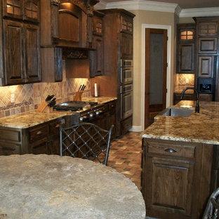 ニューオリンズの大きいトラディショナルスタイルのおしゃれなキッチン (濃色木目調キャビネット、エプロンフロントシンク、レイズドパネル扉のキャビネット、珪岩カウンター、ベージュキッチンパネル、トラバーチンのキッチンパネル、シルバーの調理設備、レンガの床、赤い床) の写真