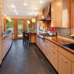 Example of a trendy galley enclosed kitchen design in Portland with an undermount sink, flat-panel cabinets, medium tone wood cabinets, granite countertops, gray backsplash, glass sheet backsplash, stainless steel appliances and orange countertops