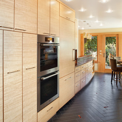 Trendy kitchen photo in Portland with stainless steel appliances, flat-panel cabinets and medium tone wood cabinets
