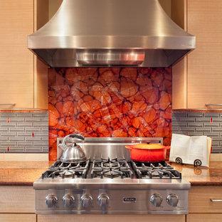 Idéer för ett modernt kök, med rostfria vitvaror, släta luckor, skåp i mellenmörkt trä, rött stänkskydd och glaspanel som stänkskydd