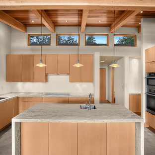 Contemporary kitchen inspiration - Example of a trendy l-shaped concrete floor kitchen design in Seattle with an undermount sink, flat-panel cabinets, light wood cabinets, stainless steel appliances and an island