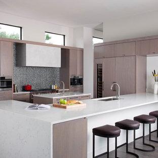ローリーの大きいモダンスタイルのおしゃれなキッチン (ドロップインシンク、フラットパネル扉のキャビネット、淡色木目調キャビネット、大理石カウンター、グレーのキッチンパネル、セラミックタイルのキッチンパネル、シルバーの調理設備の、淡色無垢フローリング、茶色い床) の写真