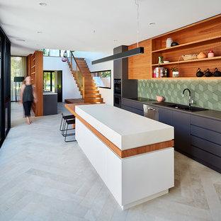 メルボルンのコンテンポラリースタイルのおしゃれなキッチン (ダブルシンク、フラットパネル扉のキャビネット、黒いキャビネット、人工大理石カウンター、緑のキッチンパネル、磁器タイルのキッチンパネル、シルバーの調理設備、磁器タイルの床) の写真