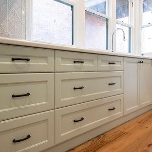 メルボルンの広いヴィクトリアン調のおしゃれなキッチン (ドロップインシンク、シェーカースタイル扉のキャビネット、緑のキャビネット、クオーツストーンカウンター、白いキッチンパネル、ガラスまたは窓のキッチンパネル、黒い調理設備、無垢フローリング、白いキッチンカウンター) の写真