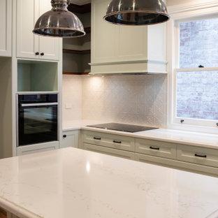 メルボルンの広いヴィクトリアン調のおしゃれなキッチン (シェーカースタイル扉のキャビネット、緑のキャビネット、クオーツストーンカウンター、白いキッチンパネル、メタルタイルのキッチンパネル、黒い調理設備、白いキッチンカウンター、ドロップインシンク、無垢フローリング) の写真
