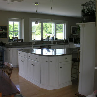 Large traditional l-shaped eat-in kitchen in Portland Maine with an undermount sink, louvered cabinets, white cabinets, granite benchtops, grey splashback, stone slab splashback, white appliances, light hardwood floors and with island.