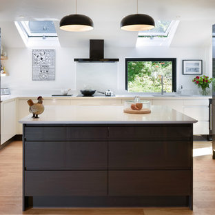 Design ideas for a large contemporary u-shaped kitchen/diner in Cornwall with grey cabinets, granite worktops, white splashback, an island, white worktops, integrated appliances, brown floors, a submerged sink, flat-panel cabinets and medium hardwood flooring.