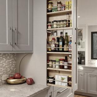 Foto på ett stort vintage grå kök, med en undermonterad diskho, skåp i shakerstil, grå skåp, bänkskiva i kvartsit, grått stänkskydd, stänkskydd i mosaik, rostfria vitvaror, mellanmörkt trägolv, en halv köksö och brunt golv