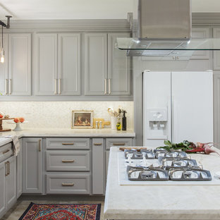 Photo of a mid-sized transitional l-shaped eat-in kitchen in San Diego with recessed-panel cabinets, grey cabinets, quartzite benchtops, white splashback, white appliances, porcelain floors, with island, beige floor, a single-bowl sink, mosaic tile splashback and white benchtop.