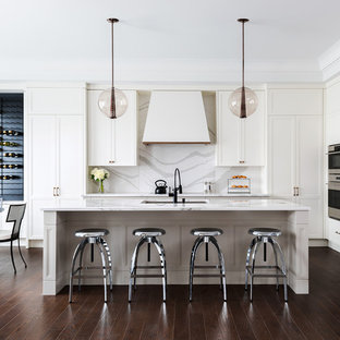 Large trendy l-shaped medium tone wood floor eat-in kitchen photo in Other with an undermount sink, recessed-panel cabinets, white cabinets, gray backsplash, stainless steel appliances, an island, marble countertops and stone slab backsplash
