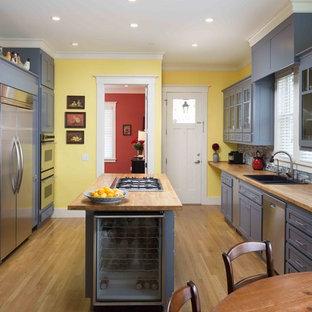 Klassische Küche mit Doppelwaschbecken, Glasfronten, blauen Schränken, Arbeitsplatte aus Holz, Küchenrückwand in Blau, Küchengeräten aus Edelstahl, hellem Holzboden, Kücheninsel und Rückwand aus Glasfliesen in San Francisco